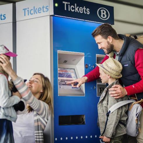 family buying train tickets on a vending machine
