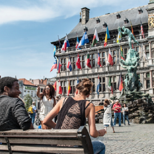 un couple de touristes assis sur un banc sur la grand place de la ville d'anvers