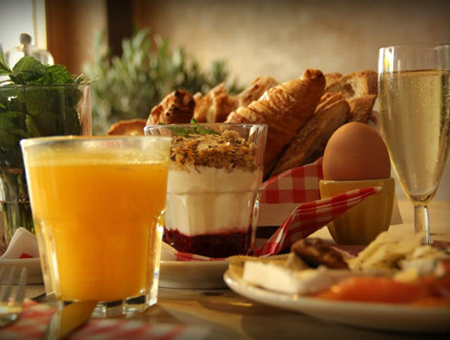 A delicious breakfast with yoghurt, fruit juice, croissants and an egg