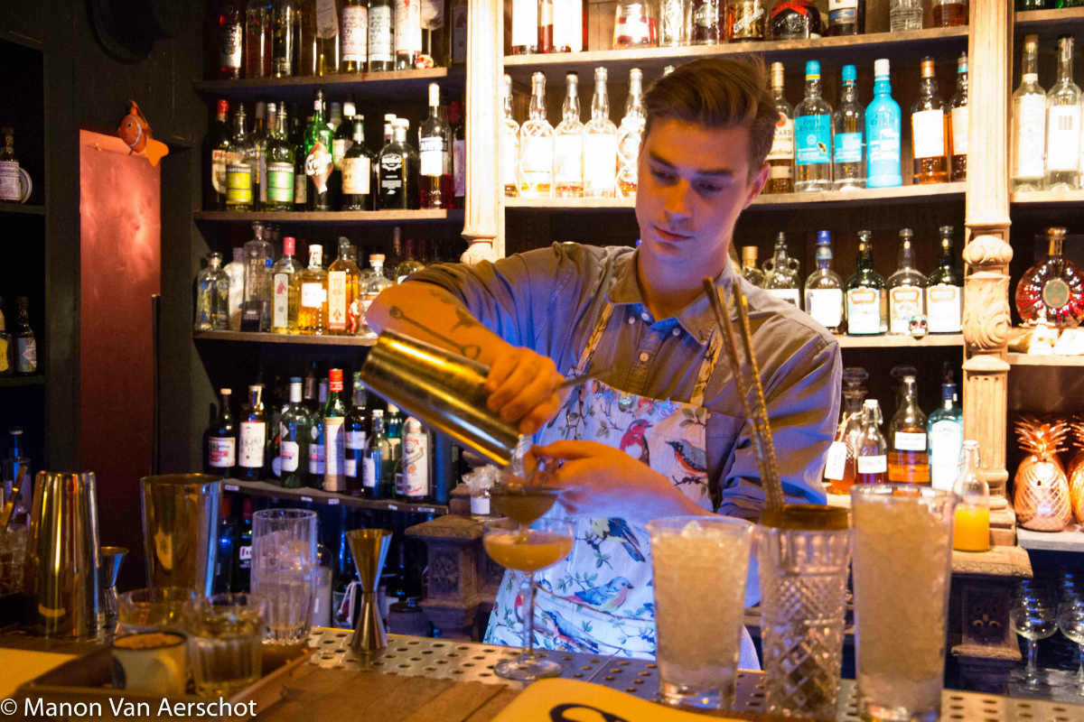 Een barman bereidt een cocktail.